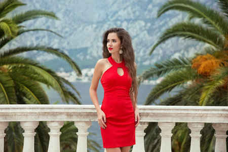 balcony view: Beautiful young sexy brunette girl in red dress posing on Balcony view on palms and sea shore Kotor, Montenegro. Stock Photo
