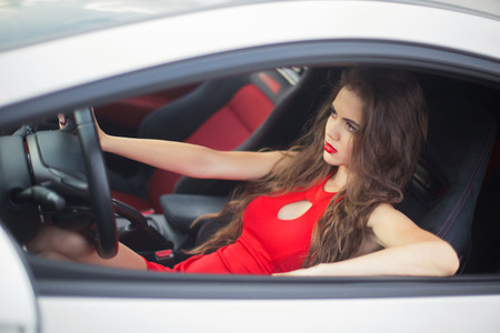 Beautiful girl driver driving in car, sensual brunette model wearing in red dress sitting in automobile. Standard-Bild