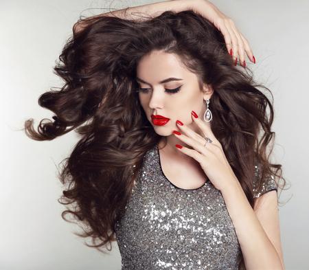 morena: Cabello largo. Maquillaje. Retrato de la muchacha hermosa. Moda mujer morena con labios rojos, uñas cuidadas, peinado rizado brillante sana posando sobre fondo de estudio.