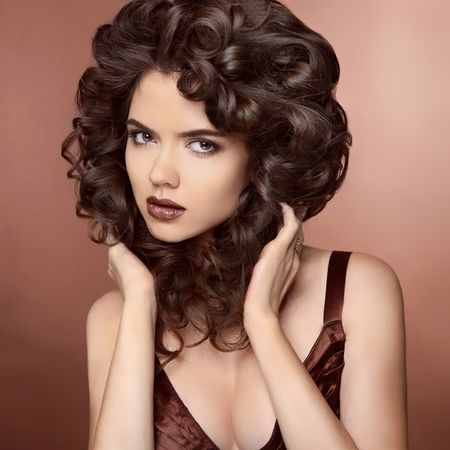 beige lips: Beauty Model girl with Healthy Brown Hair. Beautiful brunette woman touching her curly smooth shiny hair. Wavy Hairstyle. Hair cosmetics, haircare.
