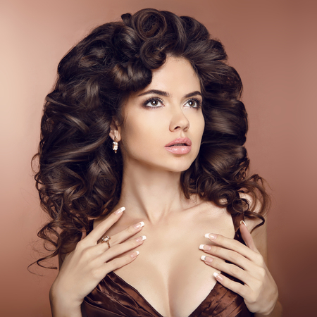 glamour makeup: Wavy healthy hair. Beauty brunette girl model with elegant hairstyle. Luxury fashion style, manicured nails, cosmetics, make-up and curly hair.