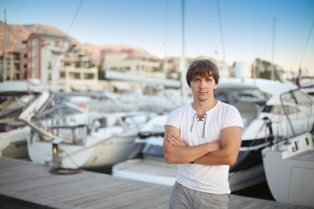 successful man: Handsome man by luxury yacht background on the beach at sunset. Outdoor portrait. Porto Montenegro.