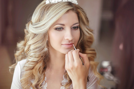 bridal salon: Beautiful bride woman with wedding makeup and hairstyle. Stylist makes make-up bride on wedding day. portrait of young woman at morning. Stock Photo