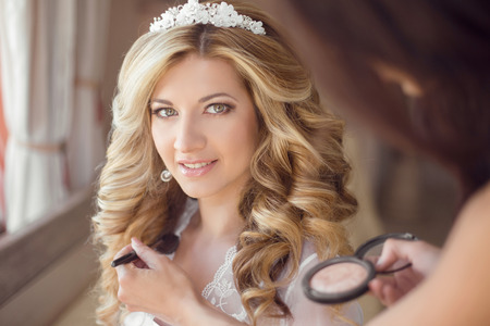 hair stylist: make up stylist. Healthy hair. beautiful smiling bride wedding portrait. Stylish makes makeup Young woman with long curly hair style. Stock Photo