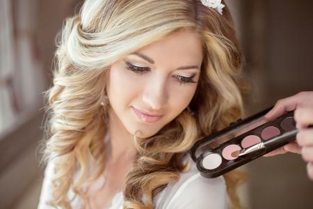 アイシャドウ パウダー化粧。長い巻き毛とまつげ女の子花嫁の魅力的な肖像画。プロのスタイリスト。