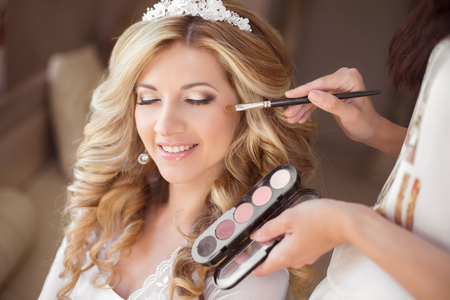 make up brushes: Beautiful smiling bride wedding portrait with makeup and hairstyle. Stylist makes make-up girl on wedding day. portrait of young woman at morning. Stock Photo