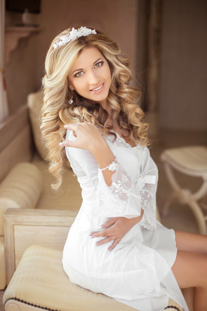 blond hair: beautiful smiling bride wedding portrait. Young woman with long curly hair style and makeup, sitting on sofa at wedding day. modern style. Stock Photo