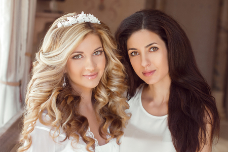 bridal salon: Healthy hair. Two beautiful girls. Brunette stylist and smiling blond girl bride with long curly hairstyle and bridal makeup. Wedding indoor portrait.