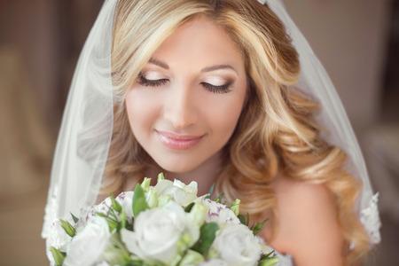 huwelijk: Mooie bruid met een bruiloft boeket bloemen. Make-up. Blond krullend kapsel. Lachende jonge vrouw. Stockfoto