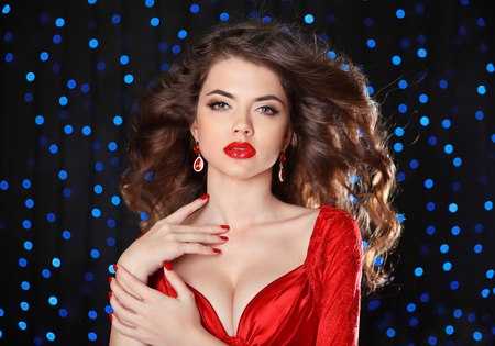 hairstyle health: Makeup. Beautiful girl model with long brown curled hair, red lips, fashion earrings luxury jewelry. Brunette lady with blowing hairstyle over holiday blue lights background.
