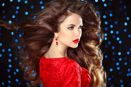 glamour woman: Hairstyle. Beautiful Brunette Girl. Fashion luxury earrings. Healthy Long Hair. Red lips. Beauty Model Woman. Elegant lady over holiday party lights background.