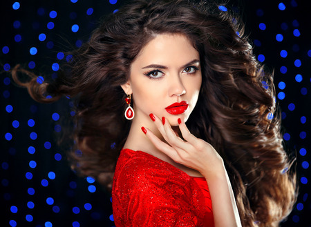 red nail colour: Hair. Beautiful brunette girl model with curly hairstyle, red lips makeup, manicured nails, luxury fashion earring jewelry. Elegant lady over holiday party lights background. Stock Photo