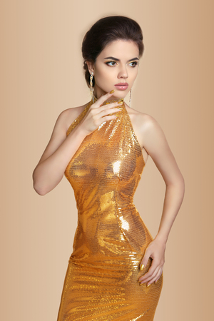 fashion dress: Fashion Elegant brunette woman in golden dress isolated on beige background. Makeup. Jewelry. Gown.