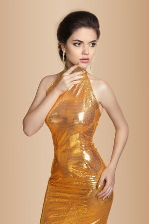 anochecer: Moda mujer morena elegante en traje de oro aislado en el fondo beige. Maquillaje. Joyería. Vestido.