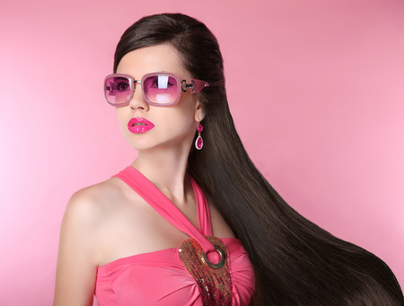 sunglasses: Beauty fashion model girl in sunglasses with bright makeup, long hair, luxury earrings jewelry. Glamour woman isolated on pink studio background. Stock Photo
