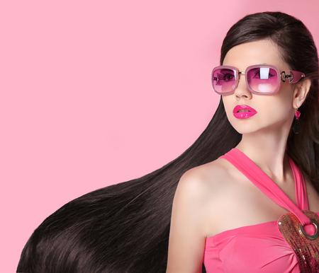 anteojos de sol: Cabello. Hermosa chica morena. Saludable largo Peinado. Gafas de sol de moda. Belleza Mujer Modelo. Persona de sexo femenino del encanto aislado en el fondo de color rosa de estudio.