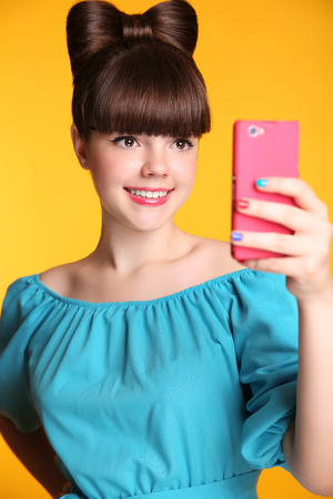 photo pictures: Happy smiling funny teen girl Taking Selfie Photo on Smart Phone. Young teenage taking pictures isolated on yellow studio background.
