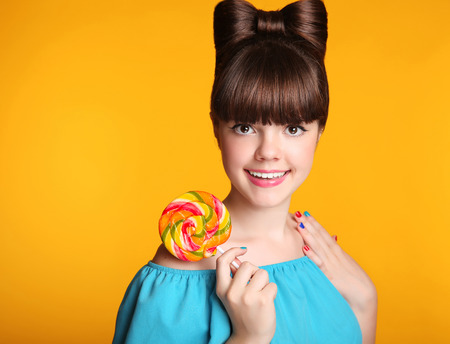 Beauty happy smiling teen girl Eating colourful lollipop. Lollypop. Surprised Young funny woman model with bow hairstyle, manicured nail art and makeup isolated on yellow background.