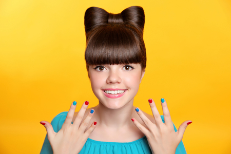 woman hairstyle: Happy smiling teen girl with bow hairstyle and colourful manicured polish nails. Funny girl showing ten fingers isolated on studio yellow background.