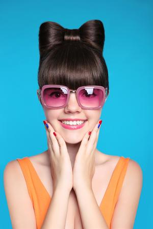弓の髪型、青い背景で分離されたファッションのピンクのサングラスを着て面白いモデルで幸せな笑みを浮かべて十代の少女。 写真素材