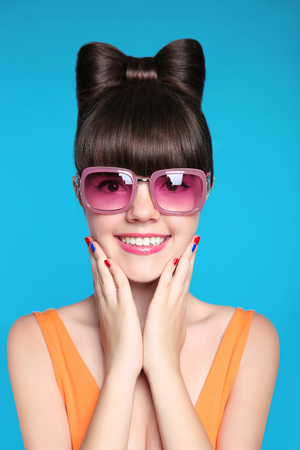 Happy smiling teen girl with bow hairstyle, funny model wearing in fashion pink sunglasses isolated in blue background. Stockfoto