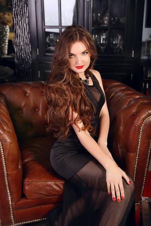 mujeres elegantes: Mujer hermosa en ropa elegante noche sentado en el sillón Chesterfield en apartamentos clásicos de época. Señora del encanto. Interior, muebles.