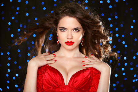 Attractive girl with makeup. Red lips. Jewelry Earring. Manicured nails. Expressive eyes stare. Elegant lady over studio blue lights on dark background. Luxury style. Stockfoto