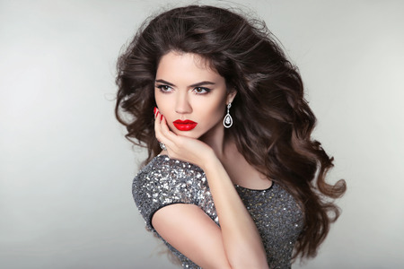 Hair. Beauty Makeup Beautiful Brunette Girl. Healthy Long Hair. Red lips. Fashion earrings jewels. Attractive Model Woman. Blowing Hairstyle.