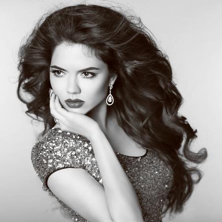 mujeres elegantes: Modelo hermoso de la muchacha elegante, con joyas, maquillaje y lon ondulado peinado del cabello. Retrato blanco y negro. Sombras grises.