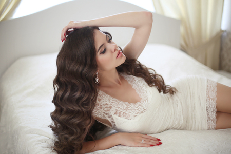 Hairstyle. Beautiful brunette bride girl with long healthy wavy hair styling in short lace wedding dress lying in white bed posing in modern interior.