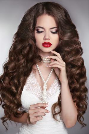 labios sensuales: Cabello largo saludable. Retrato de la belleza de una muchacha hermosa de la manera con los labios rojos y sensuales. Boda maquillaje y agitando peinado. Novia de lujo de estilo moderno.
