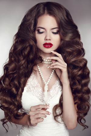 pelo largo: Cabello largo saludable. Maquillaje chica. Bella morena. Labios rojos. Collar de la joyería de la perla. Belleza Mujer Modelo. Ondulado Peinado. Foto de archivo