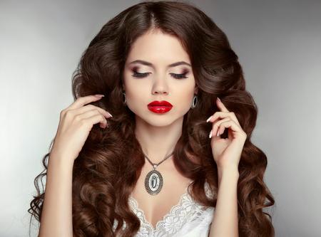pelo largo: Cabello largo. Maquillaje. Mujer hermosa con el peinado ondulado y maquillaje de la tarde. Joyería. Retrato de la belleza chica de moda. Señora elegante con colgante de diamantes.