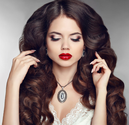 red lip: Hairstyle. Makeup. Jewelry. Beautiful woman with curly hair and evening make-up. Beauty fashion girl portrait. Elegant lady with diamond pendant. Stock Photo
