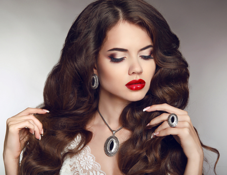 Healthy long hair. Makeup. Jewellery and bijouterie. Beautiful brunette girl model with luxury fashion earrings jewelry.