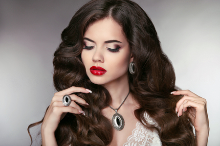Hair. Beautiful model with elegant wavy long hairstyle. Beautiful woman with fashion expensive pendant  jewelry and colourful makeup.