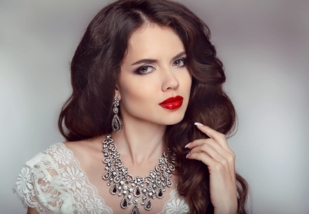 jewelry: Portrait of a beautiful fashion bride girl with sensual red lips. Wedding make up and waving hair. Studio background. Luxury modern style.