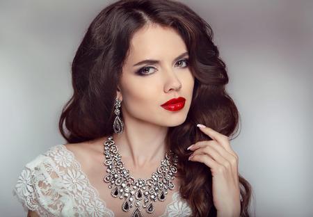 Portret van een mooie mode bruid meisje met sensuele rode lippen. Bruiloft make-up en golvend haar. Studio achtergrond. Luxe moderne stijl. Stockfoto