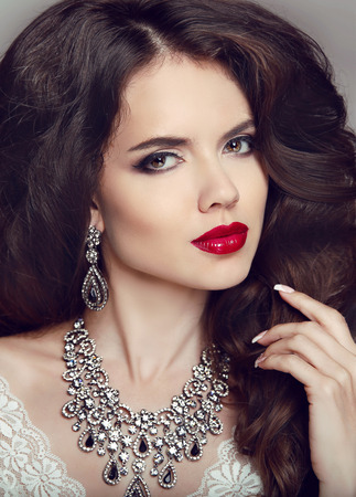 Portrait of beautiful brunette woman with red lips, long healthy wavy hair, luxury jewelry.