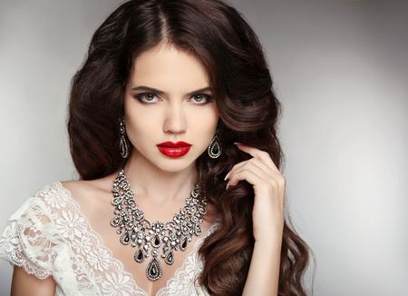 Kapsel. Bedenken. Sieraden. Mooie vrouw met krullend haar en avond make-up. Schoonheid portret mode meisje. Elegante dame met diamanten hanger.
