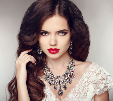 long red hair woman: Fashion earrings and Necklace. Beauty girl portrait. Hairstyle. Makeup. Jewelry. Beautiful woman with curly hair and evening make-up.