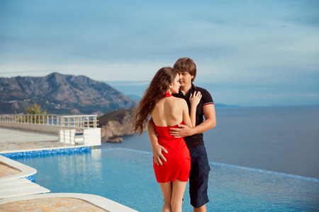 summer dress: Fashion young couple portrait, romantic lovers in love posing against the infinity  swimming pool over sea and blue sky. Resort. Travel Vacation. Handsome man hugging Beautiful woman in red dress.