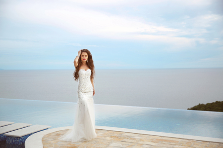 Beautiful bride girl in beaded wedding dress. Summer holiday fashion concept. Luxury resort woman posing by infinity swim pool over blue sky with clouds. Stockfoto