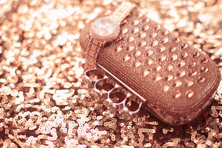 Luxury women accessories. wristwatch and purse, on golden sequins sparkling sequined textile.