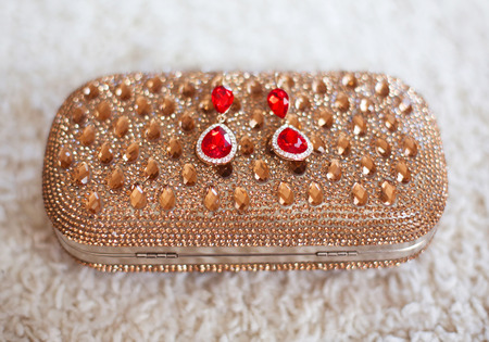strass: fashion earrings style red jewels with diamonds on golden purse with strass and gems. Stock Photo