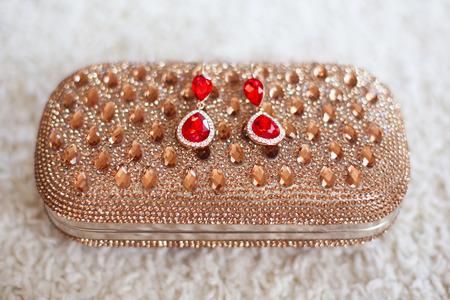 Mode-Ohrringe mit roten Rubinen Juwelen und Diamanten auf goldenen Handtasche mit Strass und Edelsteinen. Standard-Bild - 47933867