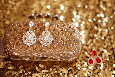 sequined: Diamond fashion earrings on golden purse with strass and gems. sequins sparkling sequined textile Stock Photo