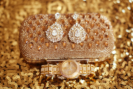 jewlery: Fashion diamond earrings and golden wristwatch, womens accessories precious Gem Jewel Set on sequins sparkling sequined textile. Stock Photo