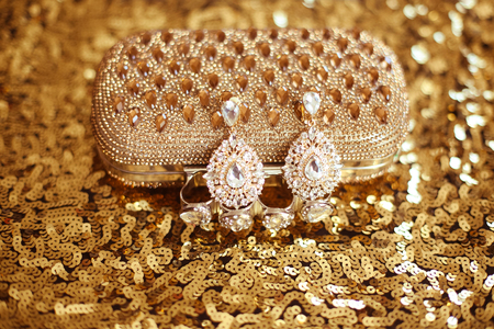 jewlery: Precious Gem fashion earring with diamonds gems with Shiny Crystal purse on sequins sparkling sequined textile. Womens accessories.