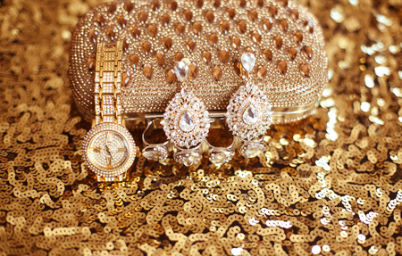 sequined: Fashion diamond earrings and golden wristwatch, womens accessories precious Gem Jewel Set on sequins sparkling sequined textile. Stock Photo